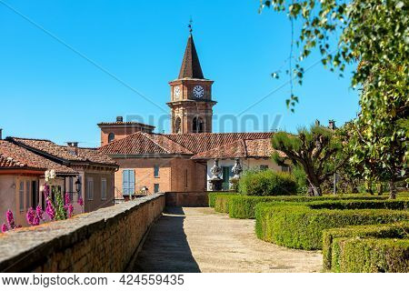 Park with green trees and bushes, houses with red roofs and brick belfry under blue sky in small town of Govone in Piedmont, Northern Italy.