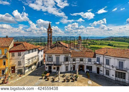 Small town square surrounded by houses with red roofs and belfries on background in Govone - comune overlooking green hills under blue sky with white clouds in Piedmont, Northern Italy.