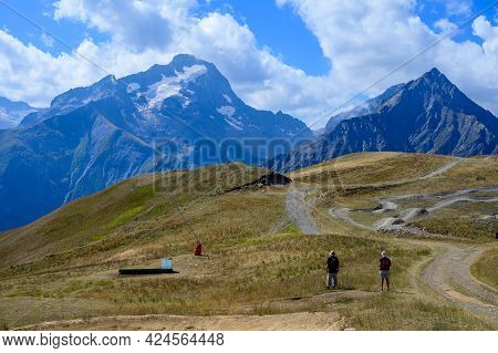 Old Man And Woman Hiking In Ecrins Alpine Mountain Range In Summer, Les Deux Alpes, France