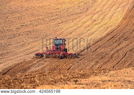 A Heavy Crawler Tractor Plows And Buries A Field In Early Spring, A Plowed Field For Crops 1.