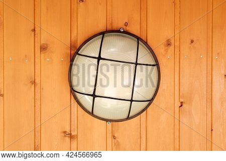 A Round Lamp With A Glass Shade And A Mesh Holder Is Screwed To The Ceiling, Sheathed With Wooden Cl