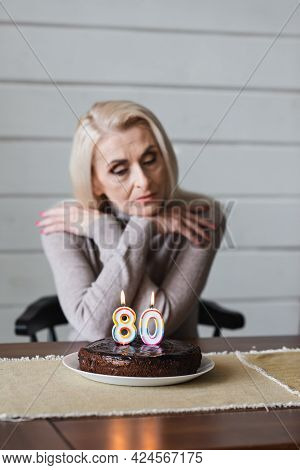 Birthday Cake With Candles In Shape Of Eighty Numbers On Table Near Blurred Senior Woman