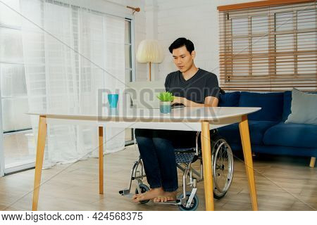 Asian Handicapped Man In A Wheelchair Uses His Abilities To Efficiently Work On A Laptop Computer On
