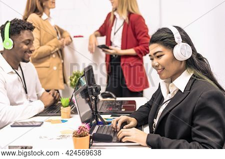 Attractive Asian Young Confident Businesswoman Sitting At The Office Table With Group Of Colleagues