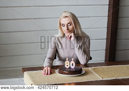 Lonely Woman Looking At Birthday Cake With Candles In Shape Of Eighty Numbers