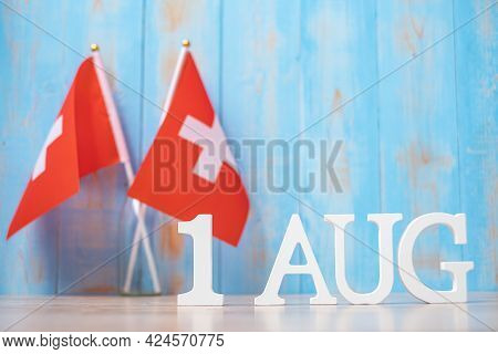 Wooden Text Of August 1st With Miniature Switzerland Flags. Switzerland National Day And Happy Celeb