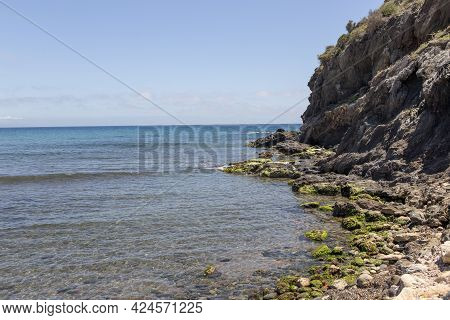 Rocks And Cliffs Seen From Below At The Edge Of A Sea Of Transparent Waters On The Spanish Mediterra
