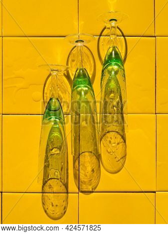 Wet Crystal Green Glasses On Yellow Bar Tile Background With Harsh Shadow. Refreshing Summer Drinks.