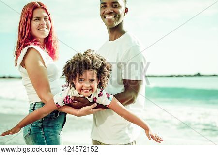 Happy Multiethnic Family, Daughter Simulating Flying With Her Arms. Summer, Holiday And Family Conce