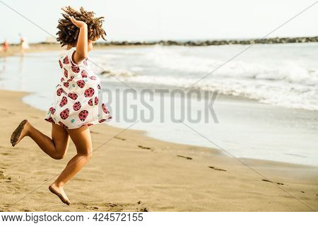 African Child Having Fun On The Beach. Portrait Of Beautiful Little Girl Celebrating The Arrival Of
