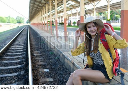 Asian Traveller With Red Backpack And Her Hat Sitting On Train Railway.