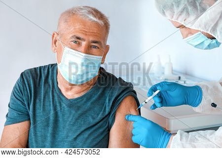 Doctor Vaccinating Senior Man In Clinic. Elderly People Vaccination. Doctor Giving Covid 19 Coronavi