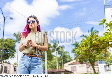 Latina Woman In Urban Environment With Fingers Together. Concept Of Non-verbal Communication