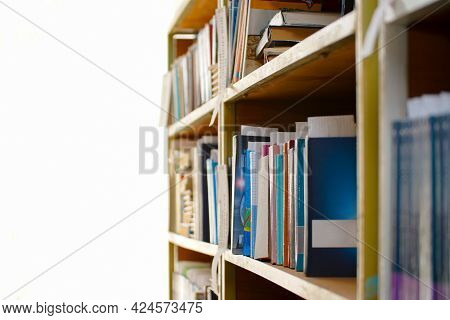 Books On A Shelf In The Library On A Light Background. Selective Focus