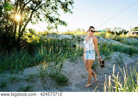 Summer Vibes! Cool Young Woman Enjoying Life. Happy Pretty Girl Walking On Beach Boardwalk At Sunset