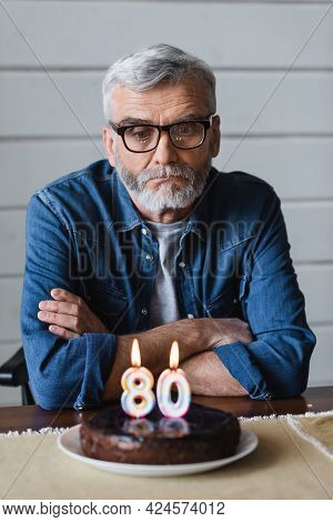 Lonely Man In Eyeglasses Sitting Near Blurred Birthday Cake With Candles In Shape Of Eighty Numbers
