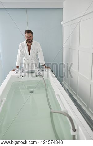 Happy Patient In Bathrobe Leans Onto Hydro Massage Tub Full Of Clear Water In Spa Salon