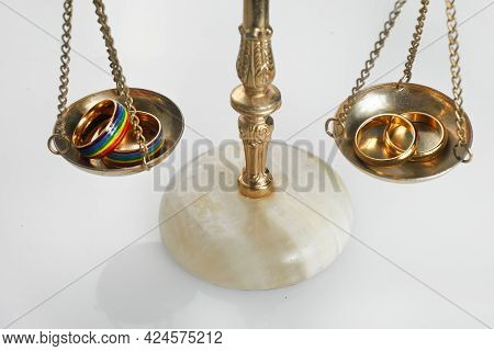 Two Gold Wedding Rings With Lgbt Rainbow Colours And Traditional Wedding Golden Rings On Scale. Homo