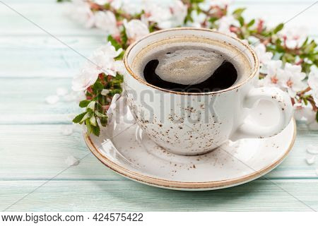 Morning espresso coffee cup on wooden table and cherry blossom