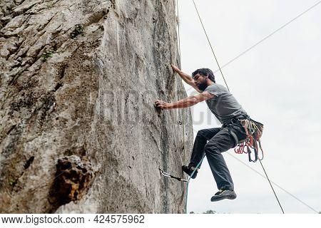 Rock Climber Climbing A Vertical Wall Wall In The Mountain. Risk Sport. Mountain Activity