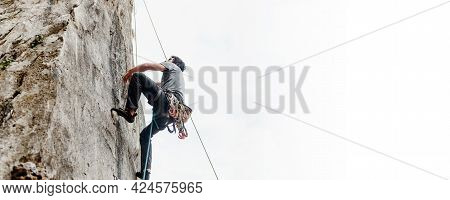 Rock Climber Climbing A Vertical Wall Wall In The Mountain. Risk Sport. Mountain Activity. Image Wit