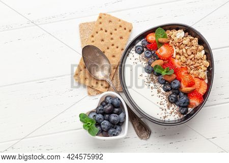 Healthy breakfast with bowl of granola, yogurt and fresh berries. Fitness protein meal. Top view flat lay with copy space