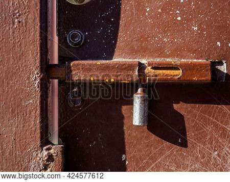 A Closed Iron Latch On The Brown Metal Door Protects Against Outside Intrusion.