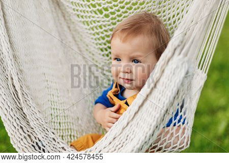 A Little Boy Sits In A Hammock On A Summer Day In The Garden
