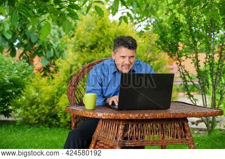Smiling Positive Middle-aged Businessman Reading Good Finance News Using Laptop Sitting In His Backy