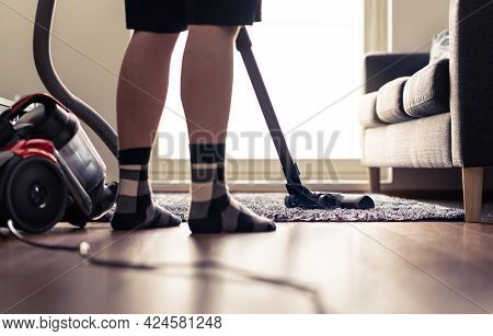 Man Cleaning Carpet And Floor With Vacuum Cleaner At Home. Happy Person Vacuuming Living Room Rug. T