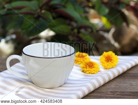 Cozy Autumn Morning Breakfast In The Garden. A Steaming Cup Of Hot Coffee, Tea And Tagetes Flowers I