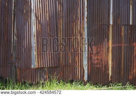 The Old Weathered And Distressed Rusty Corrugated Zinc Wall With Green Grass