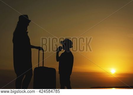 Mother And Young Son With A Suitcase On The Background Of The Sea Sunset .a Trip To The Sea, A Vacat