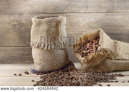 Roasted Coffee In Two Bags On A Wooden Background. Coffee Beans Have Fallen Out Into The Background.