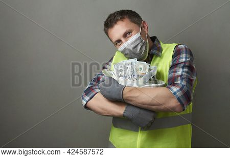 Construction Worker With A Hard Hat Full Of Dollar Money