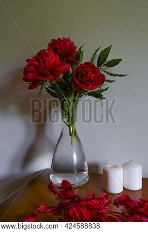 Red Peonies In Glass Vase, White Candles On Wooden Commode Across White Wall. Interior Design. Home