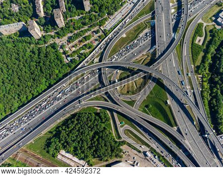 Aerial view of roads and overpasses with vehicles located near green trees in city outskirts in summer