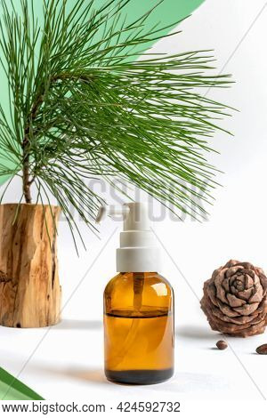 Small Glass Bottle With Dispenser Of Essential Cedar Oil, Cedar Branch And Cone On White-green Backg