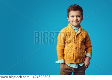 Boy Smiling While Holding Hands In Pockets, Isolated Over Blue Background