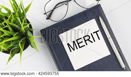 Stickers On Notebook Text Merit With Pen And Glasses On The White Background