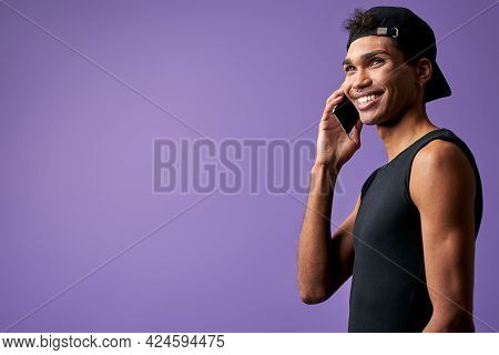 Portrait Of Transgender Brunette Man Talking On Mobile In Black T-shirt And Cap. Latino Trans Gender