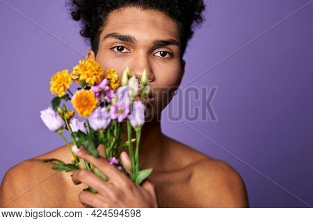 Close Up Portrait Of Transgender Man Looking Camera With Flowers In Hand. Handsome Sensual American