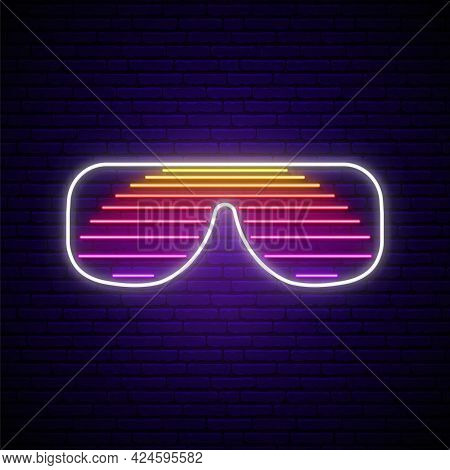 Neon Shutter Glasses Sign In Retro 80s Style. Glowing Sunglasses With Sun Reflection On Dark Brick W