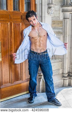 Wearing A Cross Necklace, Opening His Shirt, A Handsome, Muscular Guy Is Standing By A Old Fashion D