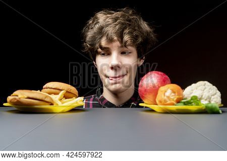 Young Male Making Choice Between Healthy Vegetables Or Junk Fast Food B