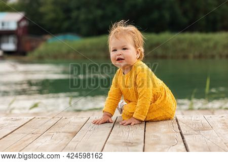 Summertime. Pretty Caucasian Smiling Baby Girl Sitting On The Pier By The River. Outdoors. The Conce