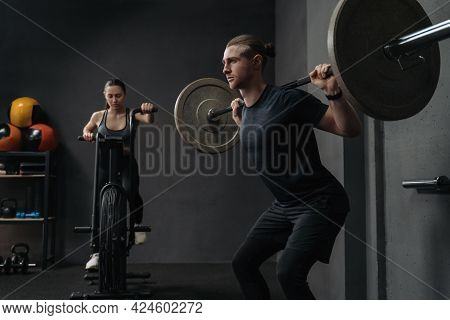Couple Have Functional Training At Gym. Attractive Fit Woman Is Working Out On Exercise Bike, While