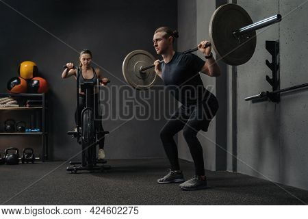 Group Functional Training. Muscular Man And Beautiful Woman Working Out With Sport Equipment In Gym.