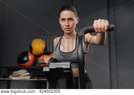 Attractive Self-confident Woman Exercising On Air Bike, Burning Calories, Looking Forward, Trying Ha