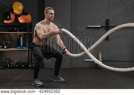 Muscular Shirtless Man Working Out With Heavy Battle Ropes At Sport Gym. Full Length Portrait Of Han